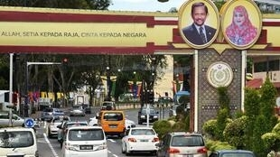 A road in Bruneï, with public portraits of Sultan Hassanal Bolkiah and Queen Saleha.