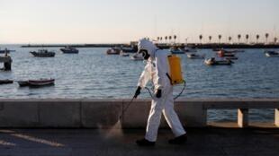 Un employé municipal désinfecte les rues de la ville portugaise de Cascais, pour lutter contre l'épidémie de coronavirus, le 28 mars 2020.