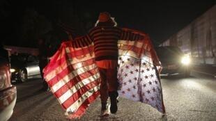Un manifestant arborant un drapeau américain lors d'une manifestation à Oakland (Californie) réclamant la justice pour Michael Brown, le jeune Noir abattu par un policier le 9 août 2014 à Ferguson.