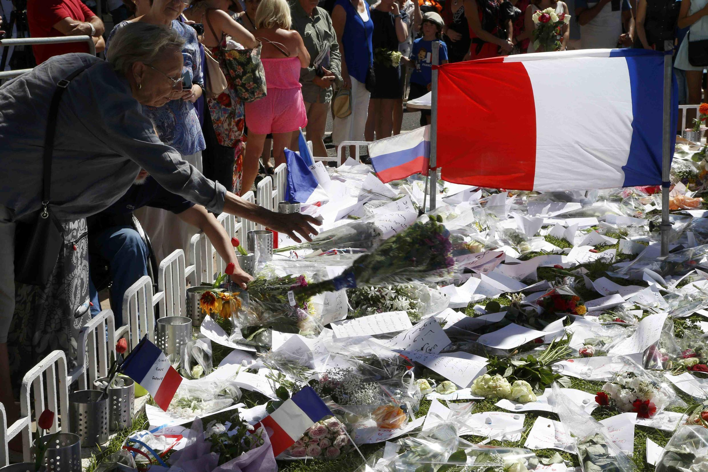 A woman places a bouquet of flowers near French flags placed in tribute to victims of the attack in Nice.