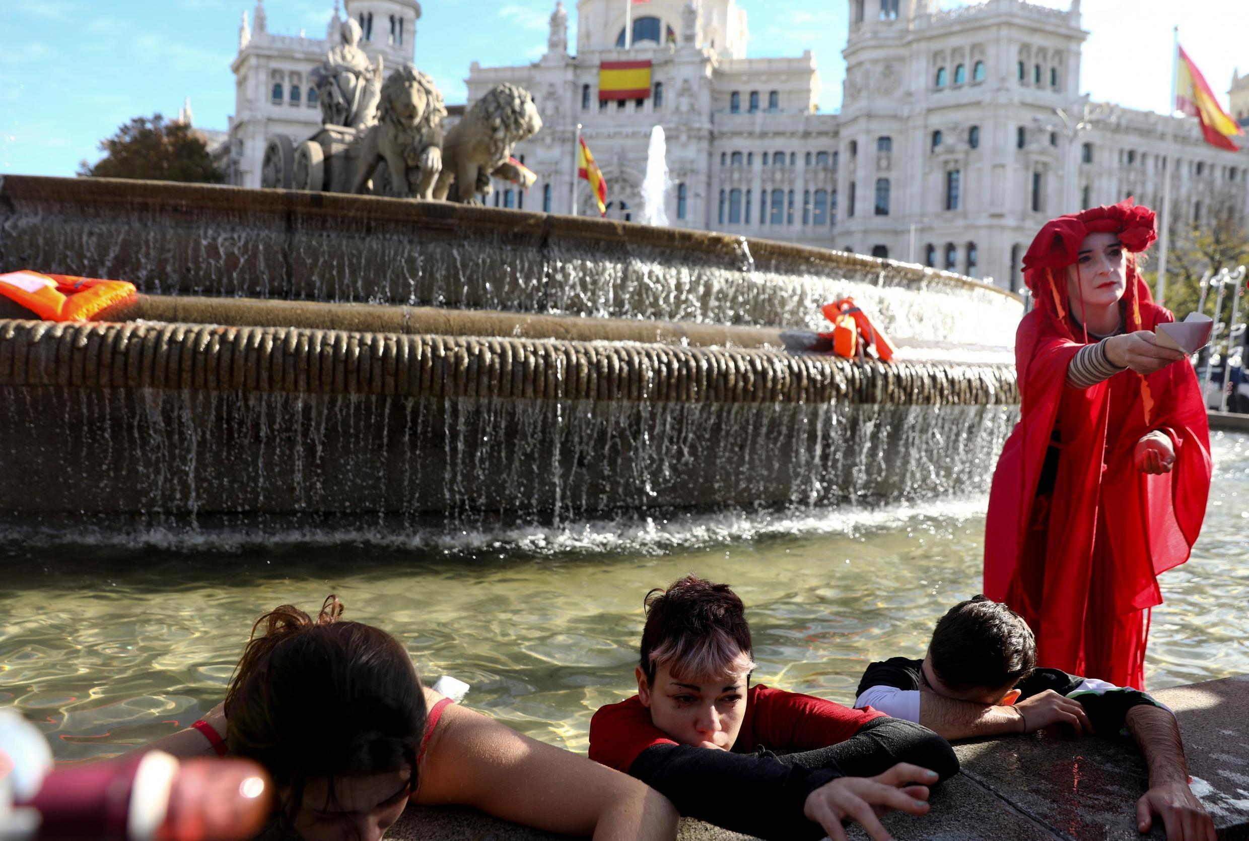 Members of Extinction Rebellion group stage a protest at Cibeles Fountain during the U.N. climate change conference (COP25) in Madrid, Spain, December 3, 2019.