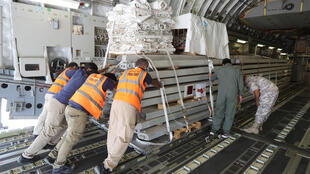 Workers load a plane as Qatar begins sending field hospital and medical aid to Lebanon from the al-Udeid airbase on August 5, 2020 on the outskirts of Doha