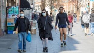 Des passants portant des masques par mesure de précaution contre le Covid-19, à Dublin, le 25 mars 2020.