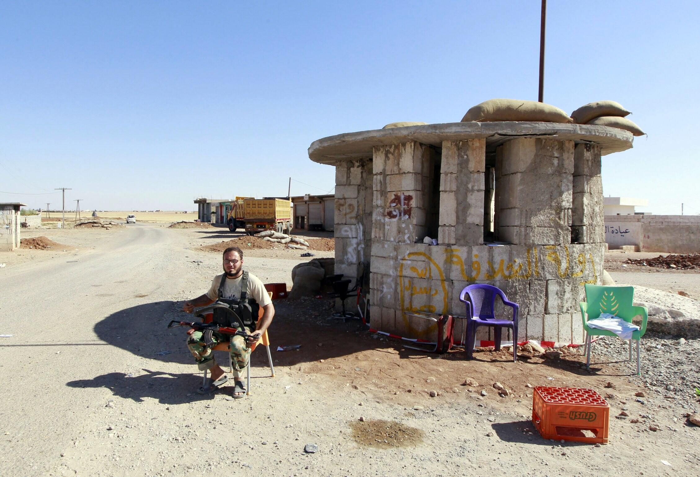 An Islamic State fighter sits at a checkpoint near Kobani, 7 October 2014.