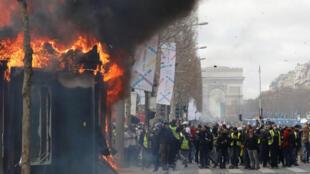 Banca de jornais é incendiada na avenida Champs-Elysées, com o Arco do Triunfo ao fundo