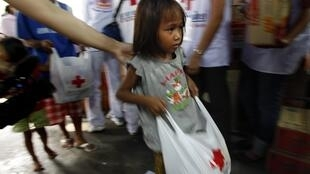 A young girl carries a medical kit being handed out to Red Shirt