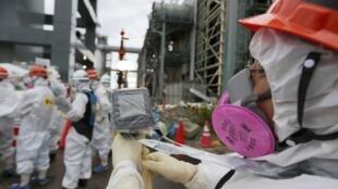 Một nhân viên của Tepco đo độ phóng xạ bên ngoại lò phản ứng số 3, nhà máy điện Fukushima