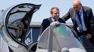 French President Emmanuel Macron in a Rafale jet fighter helped by Dassault Aviation CEO Eric Trappier (R)at the Le Bourget air show on Monday