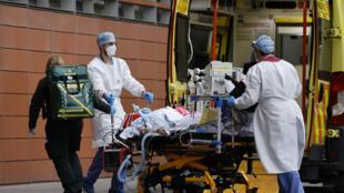 Personal médico saca de una ambulancia a un paciente en camilla a las puertas del hospital Royal London, el 19 de enero de 2021 en Londres