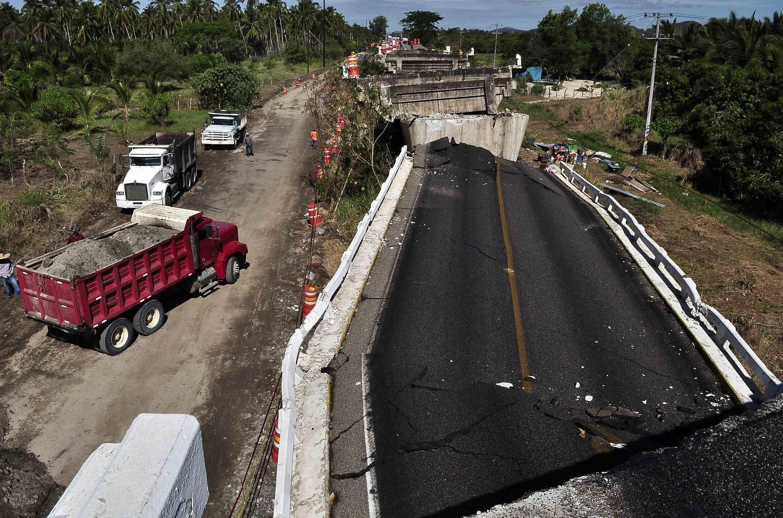 Caminhões de areia passam ao lado de ponte destruída pelo terremoto de 8 de maio de 2014, em Tecpan de Galeana