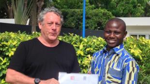 Patrick Jaquin remet le prix à Claude Romanus Biao, lauréat catégorie Poème, Prix Jeune Ecriture Francophone Stéphane Hessel.