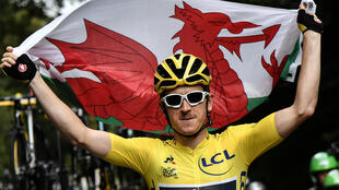 Great Britain's Geraint Thomas wearing the overall leader's yellow jersey holds the Welsh flag.