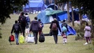 Migrantes são retirados pela polícia do acampamento de Grande Synthe, no norte da França.