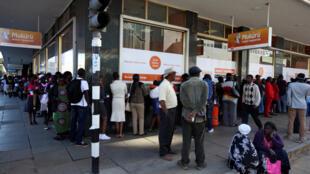 Des Zimbabwéens faisant la queue pour retirer du liquide aux distributeurs, à Harare, le 7 juillet 2016.