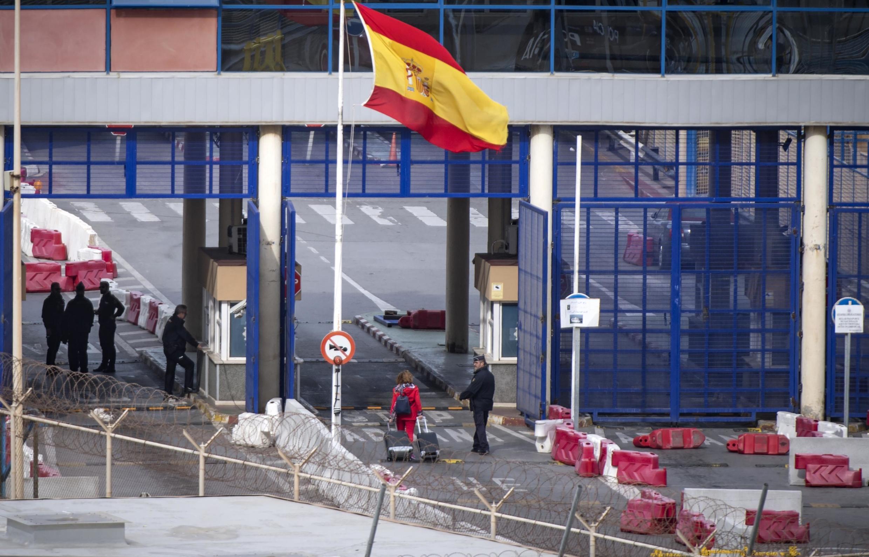 Une Espagnole franchit la frontière entre la ville marocaine de Fnideq et l'enclave espagnole de Ceuta le 13 mars 2020. Le Maroc boucle ses liaisons vers l'Espagne, la France et l'Algérie pour prévenir la propagation du coronavirus..