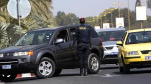 Un officier de police sénégalais inspecte des véhicules à l'entrée d'un hôtel de Dakar, le 22 janvier 2016.