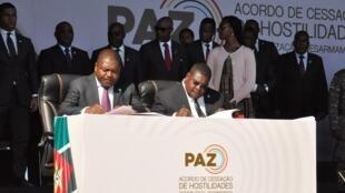 Le président du Mzambique Filipe Nyusi (g) et le leader de la Renamo Ossufo Momade signent accord de paix, au parc national de Gorongoza, le 1er août 2019.