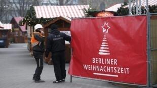 محافظان امنیتی آلمان، در محل ورودی بازار کریسمس در برلین که موقتاً تعطیل درآمده است. ٢٠ دسامبر ٢٠۱۶.