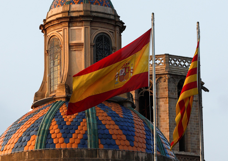 Испанский и каталонский флаги на здании парламента Каталонии утром в субботу, 28 октября — на следующий день после объявления региона о независимости