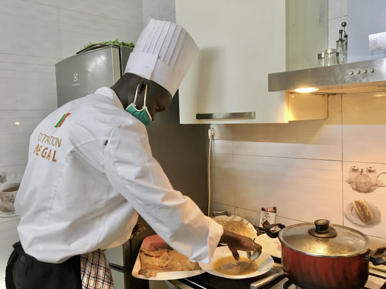 En cuisine, le chef Ousseynou Ndiaye prépare la panure du poisson.