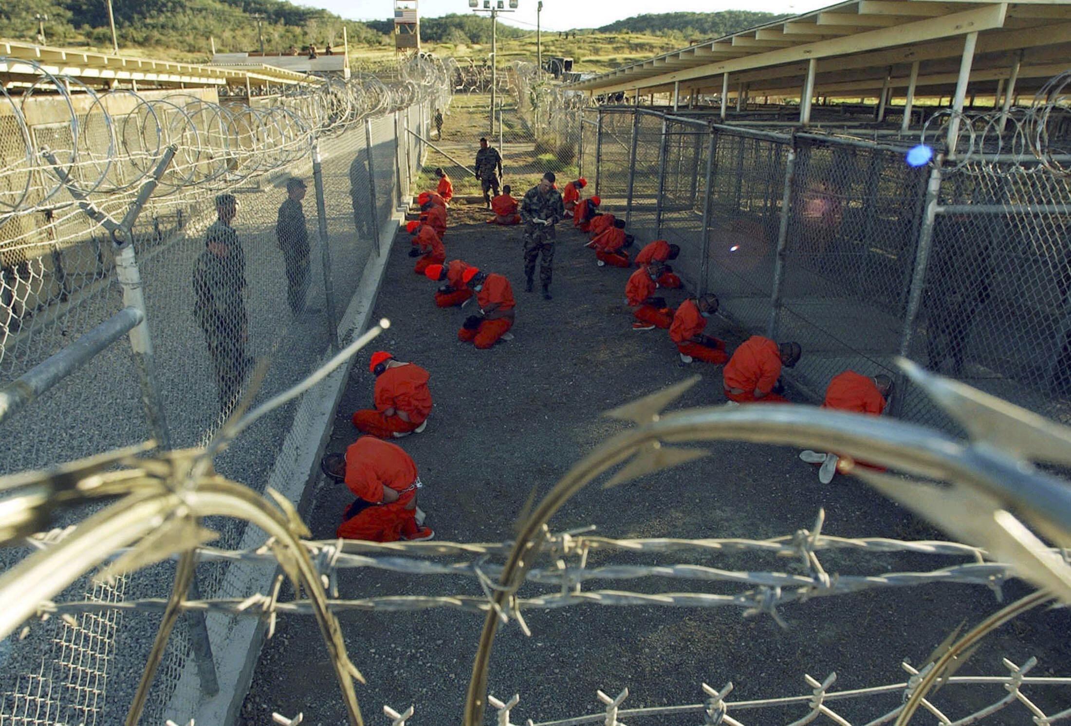 Des détenus vêtus de la tenue orange, agenouillés dans la prison à ciel ouvert de Guantanamo, à Cuba, le 11 janvier 2002.