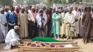 Gente se reúne alrededor de los cuerpos de víctimas de ataques del grupo yihadista Boko Haram durante la ceremonia de entierro en la aldea de Sajeri, en las afueras de la capital del estado de Borno, Maiduguri, el 8 de enero de 2019.