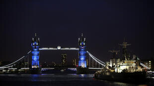 Tower Bridge is seen alternately lit in the colours of the French national flag in a tribute to the 17 people killed in the Paris terror attacks, in London, January 11, 2015.