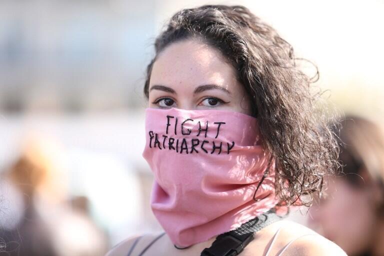 Участница движения #NousToutes с фиолетовым шарфом, на котором написано «Сражайтесь с патриархатом»