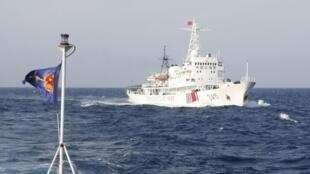 Một tàu hải cảnh Trung Quốc gần giàn khoan, phía trái là cờ của lực lượng tuần duyên Việt Nam. Ảnh chụp ngày 14/05/2014.