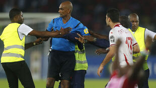 Referee Seechurn Rajindraparsad  is surrounded by security as players of Tunisia confront him after losing their quarter-final match against Equatorial Guinea