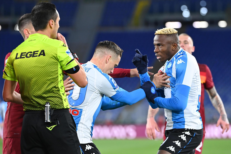 El centrocampista polaco del Nápoles Piotr Zielinski (C) frena a su compañero el delantero nigeriano Victor Osimhen (D) mientras discute con el defensor de la Roma Gianluca Mancini (atrás I) durante el partido de la Serie A italiana, el 21 de marzo de 2021, en el estadio Olimpico de Roma.