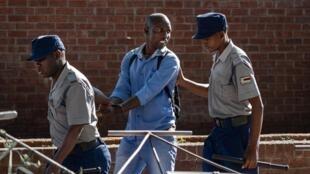 La police arrete un homme refusant de quitter un marché aux légumes à Bulawayo, au deuxième jour du confinement au Zimbabwe, le 31 mars 2020.