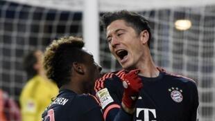 Robert Lewandowski celebrates a goal with team mate Kingsley Coman during Bayern Munich's 2-1 win at Hamburg.