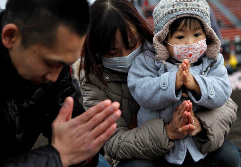 Một gia đình người Nhật cầu nguyện cho thân nhân và các nạn nhân sóng thần tại Iwaki, Fukushima - Reuters