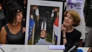 Писательница Сьюзан Джордж (справа) и экоактивистка держат перевернутый портрет Эмманюэля Макрона в Байонне перед саммитом G7