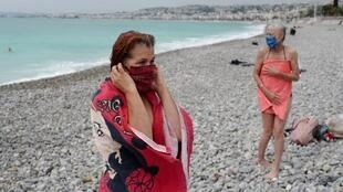 Residents of Nice enjoy a post-lockdown swim at the beach. May 2020