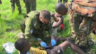 Kafunzi, province du Nord-Kivu, RDC. Un casque bleu de la Monu prodigue des soins médicaux à un milicien maï-maï capturé par les Forces armées de la RDC lors d'une opération.