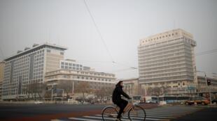 Un homme portant un masque fait du vélo alors que la Chine est frappée par une épidémie du nouveau coronavirus. Pékin, le 28 janvier 2020.