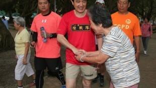 图为台湾前总统马英九晨跑接受居民问候