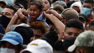 Migrantes hondureños rompen una valla policial para entrar a Guatemala en su camino a Estados Unidos, en la frontera de Corinto, Honduras, el 1º de octubre de 2020