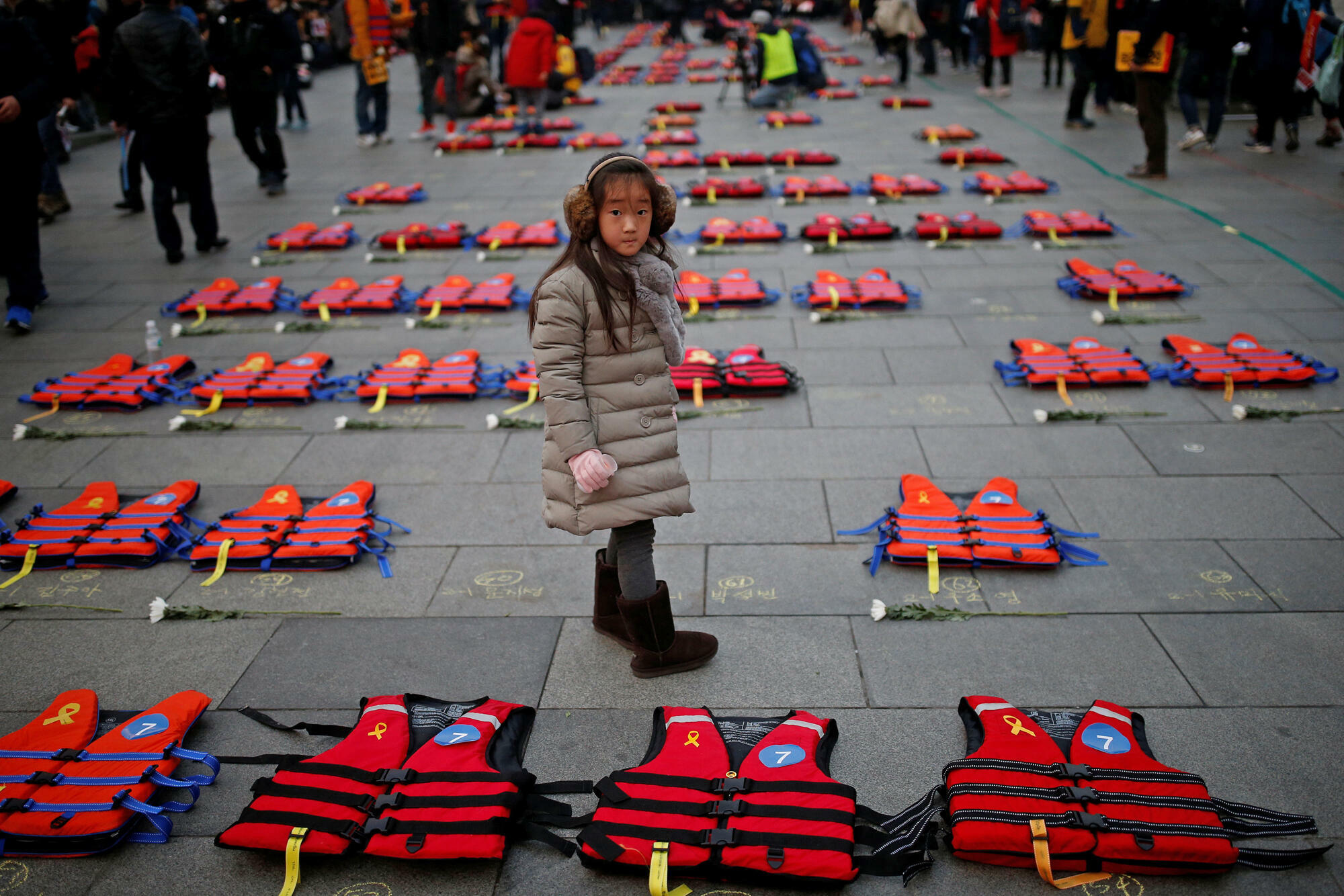 Une jeune fille se tient entre les gilets de sauvetage symbolisant les 304 victimes pendant le naufrage du ferry  Sewol lors d'une manifestation exigeant la démission de Park Geun-hye à Séoul, en Corée du Sud 17 décembre 2016.