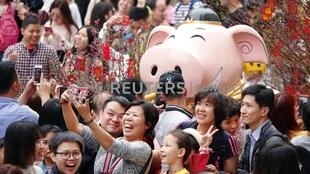 Visitors take pictures of an installation at a flower fair ahead of the Chinese Lunar New Year of the Pig, in Guangzhou, Guangdong province, China February 3, 2019. Picture taken February 3, 2019.