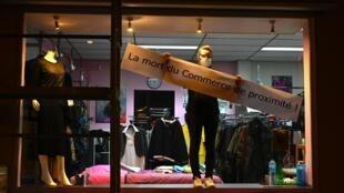 """Một tiểu thương nhân gắn biển """"Ngày tàn của các cửa hàng khu phố"""" trên tủ kính cửa hiệu quần áo để phản đối lệnh phong tỏa chống dịch Covid-19. Ảnh chụp tại thành phố Blotzheim, miền đông nước Pháp ngày 31/10/2020."""