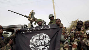 Des soldats Nigérians posent avec un drapeau de Boko Haram après avoir repris la ville de Damasak au groupe islamiste le 18 mars 2015.