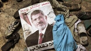 Poster do ex-presidente egípcio Mohamed Mursi entre os vestígios de uma região de protestos, no Cairo, em foto do dia 28 de outubro de 2013.