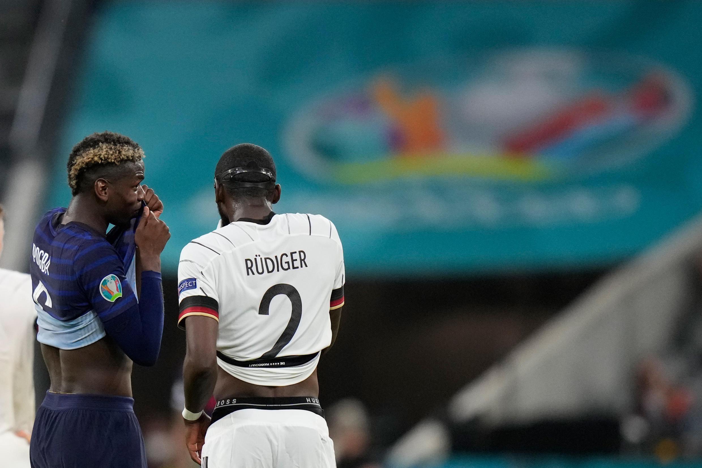 Kiungo wa kati wa Ufaransa Paul Pogba (kushoto) akizungumza na beki wa Ujerumani Antonio Ruediger wakati wa mechi yao ya Euro 2020 huko Munich
