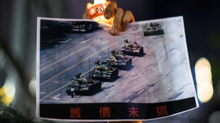 """A man holds a poster of the """"Tank Man"""" photo during a candlelit remembrance in Hong Kong's Victoria Park on June 4, 2020"""