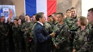 France's President Nicolas Sarkozy speaks with soldiers as he visits French troops