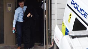 Policial acompanha mulher detida no bairro de Barking, em Londres.