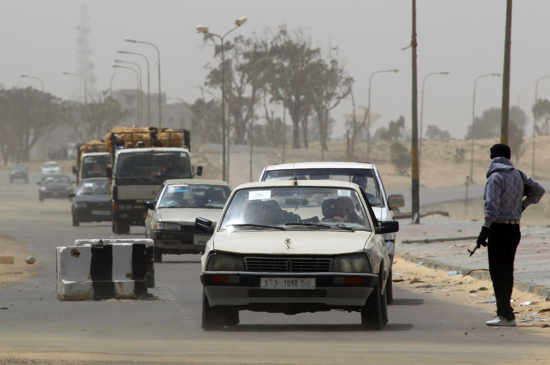 Civis fogem da cidade de Ajdabiya, atacada neste domingo pelas forças de Kadafi.